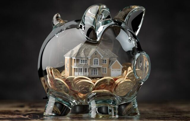 Glass piggy bank with coins and house. Mortgage, savings for real estate or to buy a house concept.